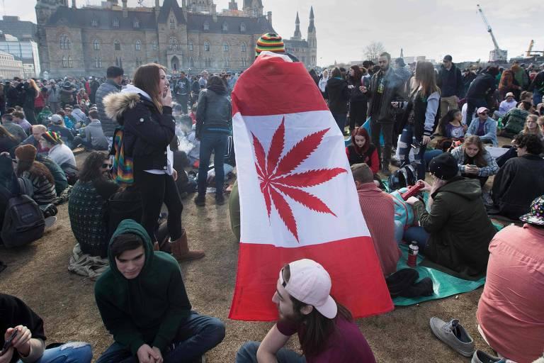Homem usando bandeira do Canadá que substitui a folha de bordo pela folha da cânabis durante a Marcha da Maconha em Ottawa, em 20 de abril