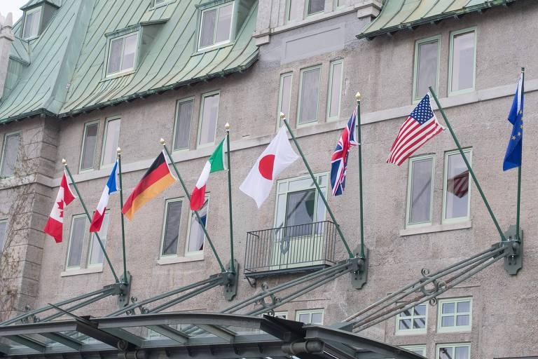 Da esquerda para a direita aparecem as bandeiras de: Canadá, França, Alemanha, Itália, Japão, Reino Unido, Estados Unidos e da União Europeia. Elas estão em mastros no prédio histórico de paredes de pedra bege e telhados esverdeados. Abaixo delas, uma estrutura de cabos de aço segura uma cúpula de vidro que faz parte da entrada do edifício, que não aparece na imagem.
