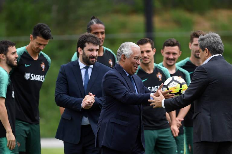 Premiê português Antonio Costa (C) recebe uma bola autografada pelos jogadores durante visita ao centro de treinamento da seleção