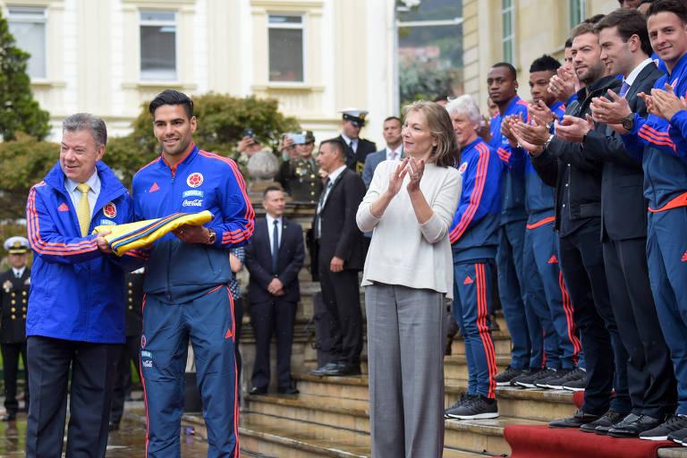 Presidente da Colômbia Juan Manuel Santos (E) entrega bandeira nacional ao jogador Radamel Falcão durante encontro antes da Copa do Mundo