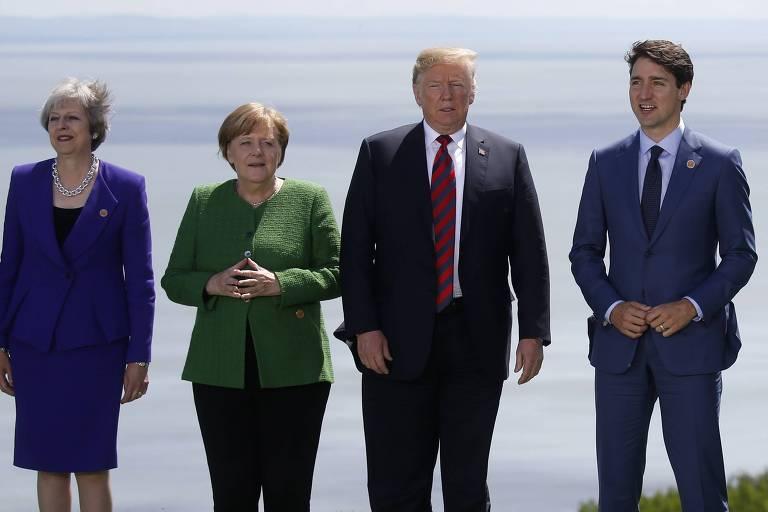 Da esquerda para a direita: Theresa May usa talleur azul e está com os braços junto ao corpo. De camisa verde e calça preta, Angela Merkel junta as mãos. Donald Trump usa terno preto, camisa branca e gravata vinho, enquanto Justin Trudeau está de terno azul, camisa branca e gravata azul.