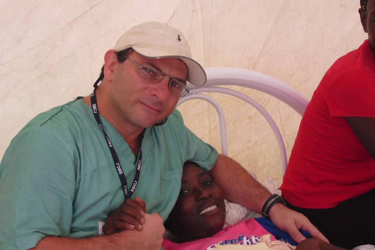O médico Fábio Racy, 49, que trabalhou dos desastres do Haiti e Porto Rico, junto a um paciente. O médico está segurando a mão de uma paciente deitada