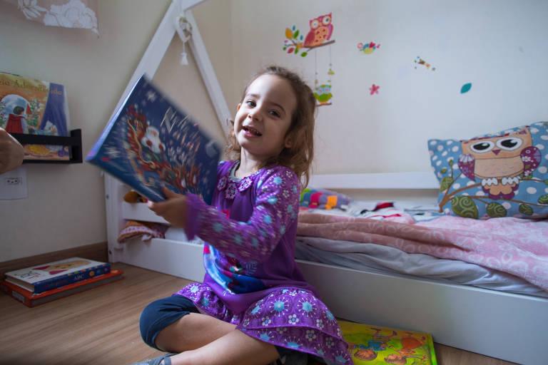 Letícia, dois anos, segura livro de história infantil