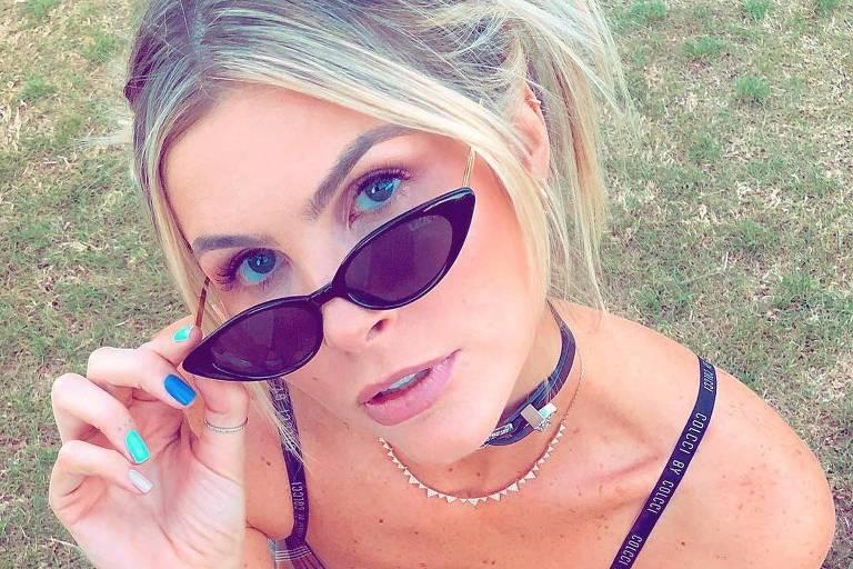 A blogueira Julia Faria sentada ajeita os óculos de sol