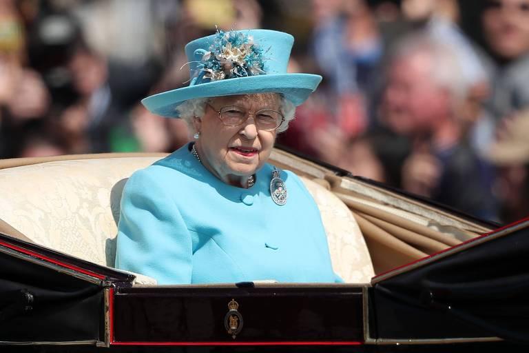 Vestida de azul e com um chapéu da mesma cor, a Rainha Elizabeth 2ª participa da parada Trooping the Colours em uma carruagem