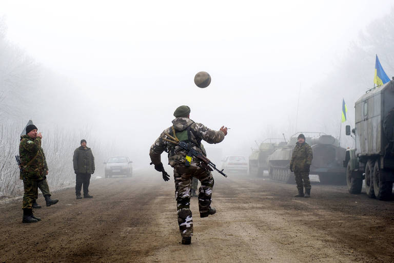 Homem armado com roupa de exército brinca com bola