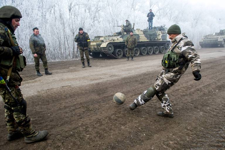 Homem com roupa de exército chuta bola em estrada de terra