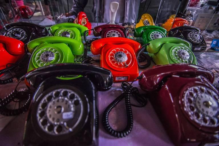 Telefones antigos coloridos em cima de mostruário