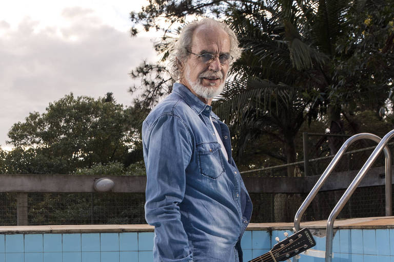 Músico Renato Teixeira caminha dentro da piscina de sua casa (sem água) na Serra da Cantareira, em São Paulo. Ele segura um violão preto com detalhe branco enquanto anda
