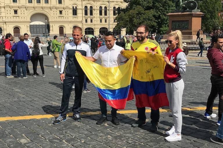 Colombianos segurando bandeira do país na Praça Vermelha com russos