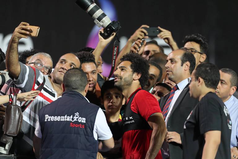 O atacante Salah tira fotos com fãs durante treino da seleção do Egito, no Cairo