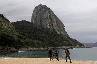 Police officers walk at Praia Vermelha beach after violent clashes with drug dealers hiding in the woods of Babilonia hill in Rio de Janeiro