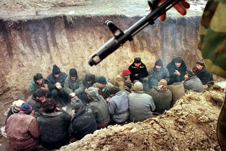 Soldados russos mantêm prisioneiros tchetchênios em trincheira durante segunda guerra na região