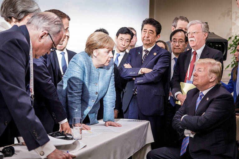 A chanceler alemã Angela Merkel, ao lado de vários chefes de Estado, falando com o presidente dos EUA, Donald Trump, que está cercado por todos eles, durante o encontro do G7