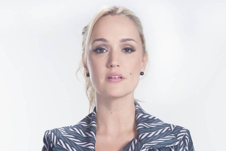 Cantora Claudia Bossle posa com vestido estampado em frente a fundo cinza claro