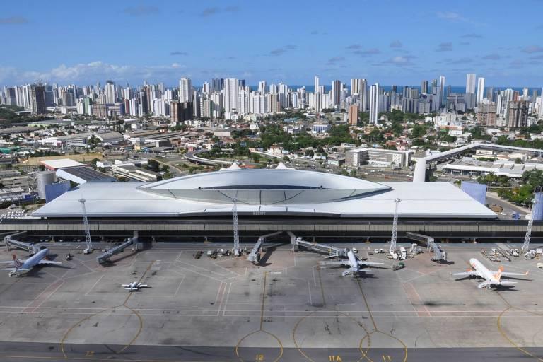 Vista aérea de aeroporto, com prédios ao fundo