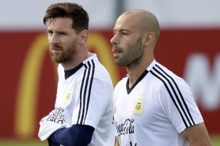 Messi coçando a barriga, ao lado esquerdo da foto, com camisa branca de treino da seleção argentina; Mascherano, ao lado direito