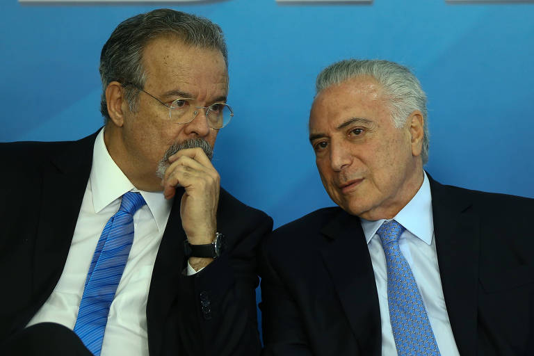 O ministros Raul Jungmann (Segurança Pública) sentado ao lado do presidente Michel Temer em cerimônia de sanção da lei do sistema único de segurança, no Palácio do Planalto.