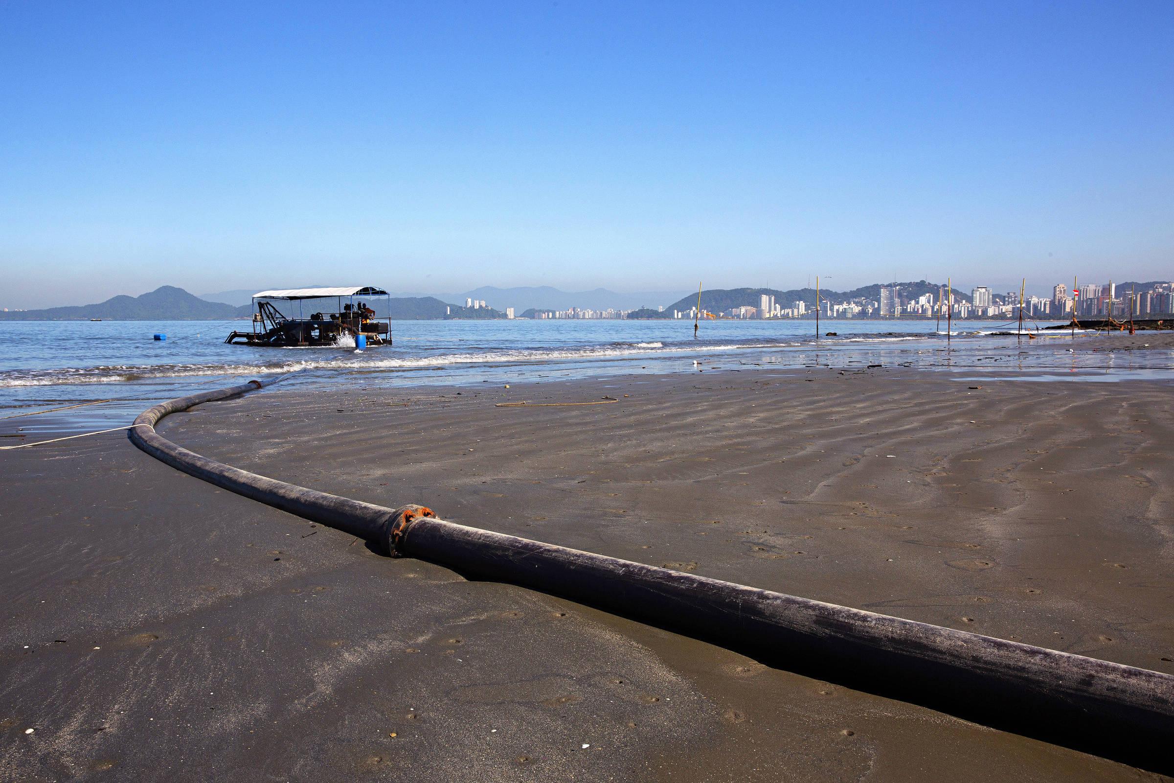 À esquerda, embarcação auxilia construção de barreira submersa em Santos para evitar a erosão marinha