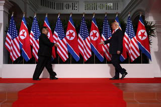 U.S. President Donald Trump and North Korean leader Kim Jong Un prepare to shake hands at the Capella Hotel on Sentosa island in Singapore