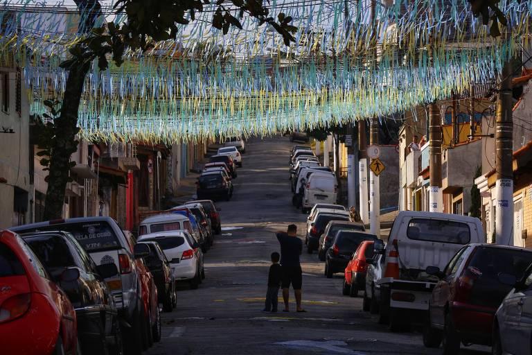 Moradores fotografam rua na zona leste de São Paulo decorada para a Copa do Mundo