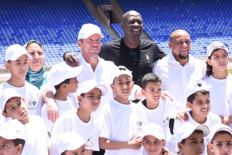 Os ex-jogadores Lothar Matthäus, de boné, Khalilou Fadiga, de preto, e Roberto Carlos posam para fotos durante visita a estádio em Marrakesh