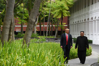 U.S. President Donald Trump and North Korean leader Kim Jong Un walk in the Capella Hotel after their working lunch, on Sentosa island in Singapore