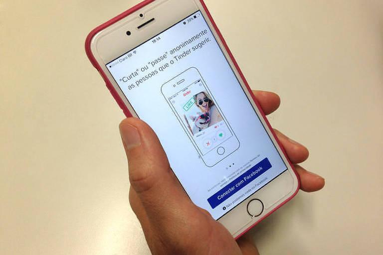 Usuário mostra aplicativo Tinder no celular