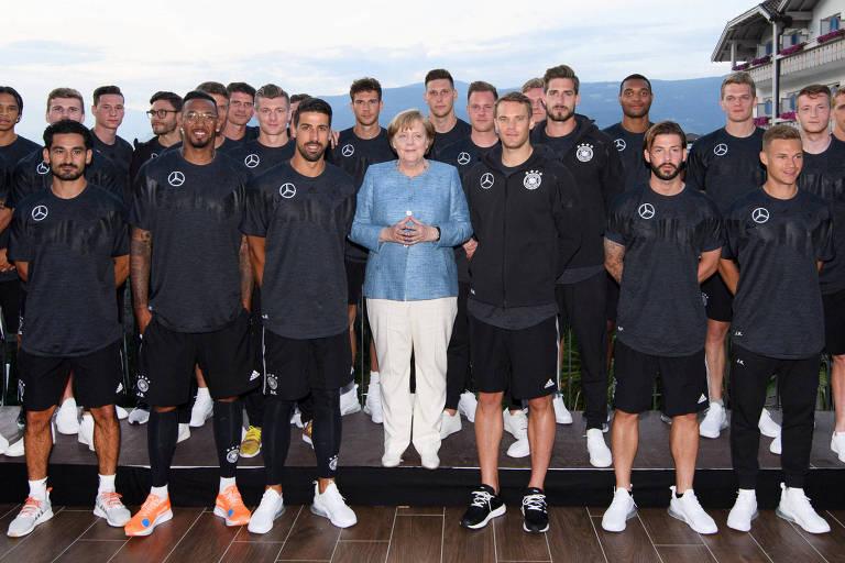 Chanceler Angela Merkel posa com a seleção da Alemanha durante visita ao centro de treinamento