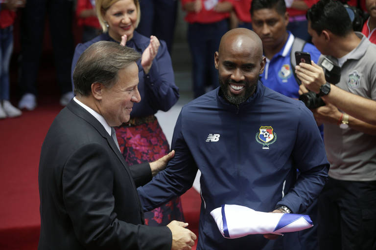 O jogador Felipe Baloy, à dir., recebe bandeira panamenha do presidente Juan Carlos Varela, durante cerimôniano palácio presidencial Las Garzas, na Cidade do Panamá