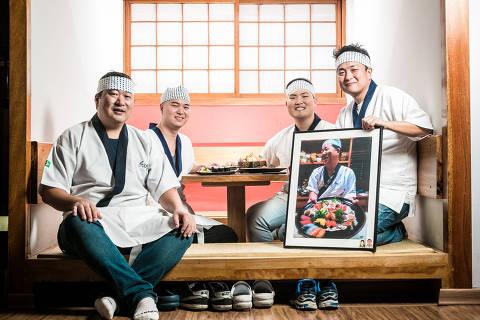 SAO PAULO - SP 11.06.2018 - Comida - Dinastia dos sushimen - Pauta para a capa de comida sobre a famílias de sushimen. Foto no restaurante Sushiguen. Na foto, (esq p/ dir) Massatoshi Shimizu (fez o usuzukuri de hirame), Takeshi Shimizu (fez o chirashi Jo), Makoto Shimizu (fez o tekkamaki) e Hideto Shimizu (fez ostras frescas) segura a foto do seu pai, o sushiman Mitsuaki Shimizu (1942 - 2017). FOTO: KEINY ANDRADE/FOLHAPRESS