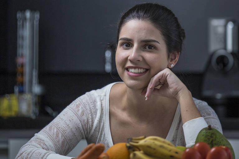 Bianca Quitério Guariglia com a mão no queixo posa com frutas