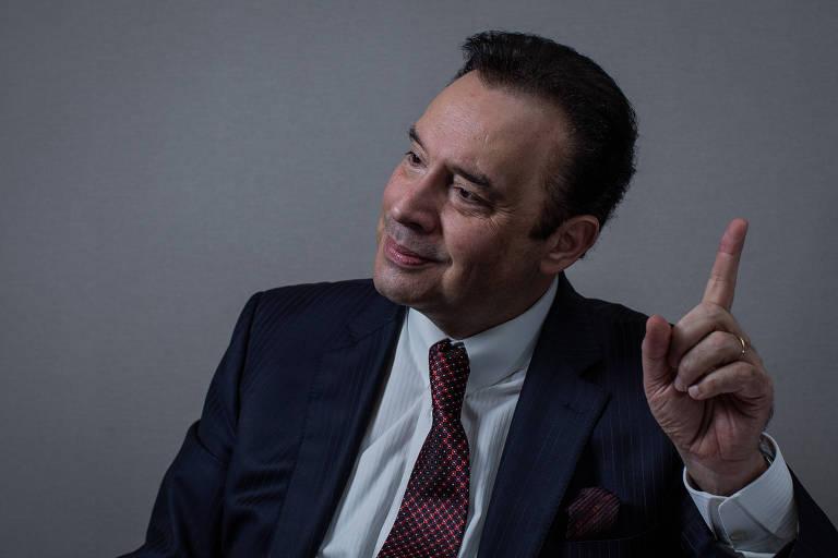 retrato do empresário com o dedo indicador erguido enquanto fala. ele usa terno preto, camisa branca e gravata vinho