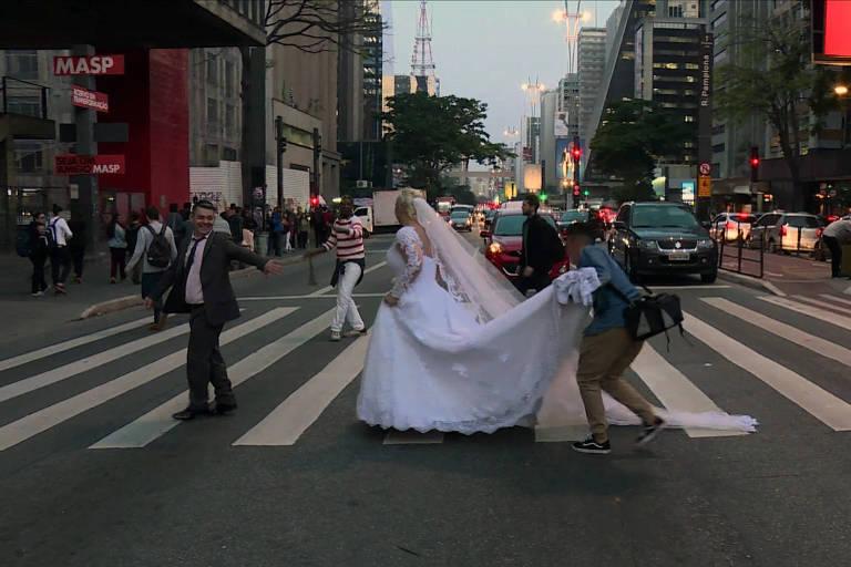 Ademir Avelino e a mulher, Glaucia Sudan, tiram fotos na avenida Paulista