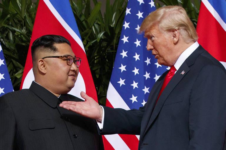 De terno cinza e gravata vermelha, Trump estende a mão enquanto fala com Kim, que usa camisa preta. Ao fundo dos dois, há bandeiras dos Estados Unidos e da Coreia do Norte.