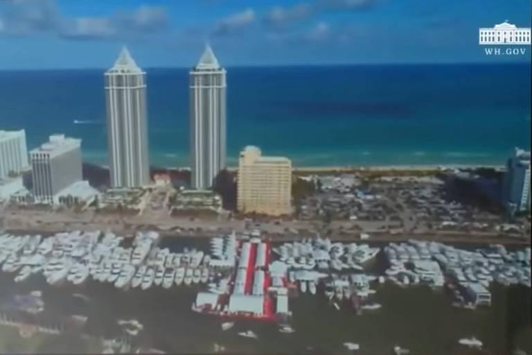 Dois prédios mais altos aparecem ao lado de construções mais baixas em uma praia de águas azuis e verdes. Ao fundo deles, casas, formando um condomínio. Imagem foi criada com computação gráfica e simula um sobrevoo a baixa altitude.