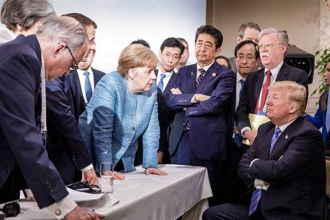 TOPSHOT - Photo released on Twitter by the German Government's spokesman Steffen Seibert on June 9, 2018 and taken by the German government's photographer Jesco Denzel shows US President Donald Trump (R) talking with German Chancellor Angela Merkel (C) and surrounded by other G7 leaders during a meeting of the G7 Summit in La Malbaie, Quebec, Canada.