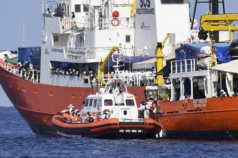 Imigrantes são transferidos do navio Aquarius para o barco do governo italiano, que ajudará no transporte até a cidade espanhola de Valencia