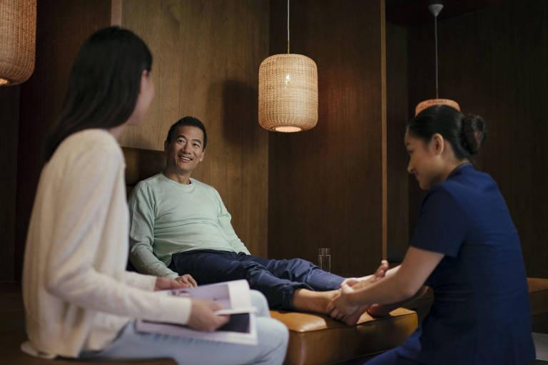 Passageiro recebe massagem nos pés no aeroporto de Hom Kong