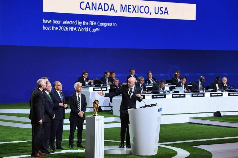 O presidente da Fifa, Gianni Infantino, ao microfone, dirige-se aos representantes da United 2026 após anúncio da candidatura vencedora