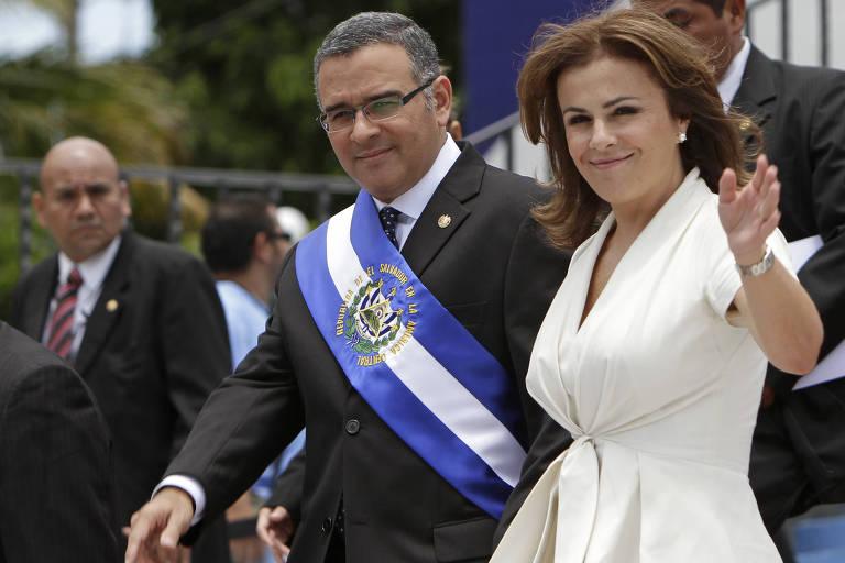 De vestido branco, Vanda acena com a mão esquerda, enquanto apoia a direita nas costas de Funes, que usa terno e a faixa presidencial de El Salvador. Os dois são cercados por seguranças.