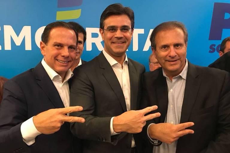 O pré-candidato João Doria fazendo gesto de campanha ao lado de políticos do DEM