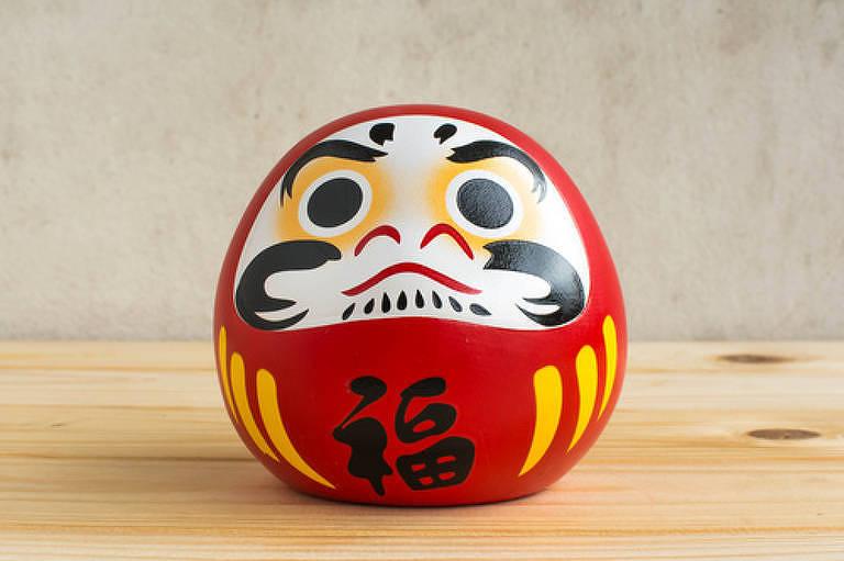 Boneco do Daruma sobre uma mesa de madeira