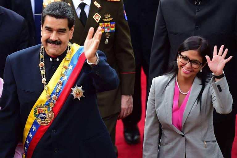 De terno preto, a faixa presidencial venezuelana e colar dourado presidencial com o escudo do país na ponta, Nicolás Maduro acena para colegas da Constituinte, ao lado de Delcy Rodríguez, que usa um terninho cinza e camisa rosa e também acena. Ambos sorriem.