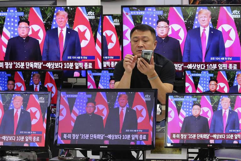 Homem mexe em seu celular entre TVs de diferentes tamanhos: duas maiores que aparecem atrás dele e três, que estão abaixo e à frente