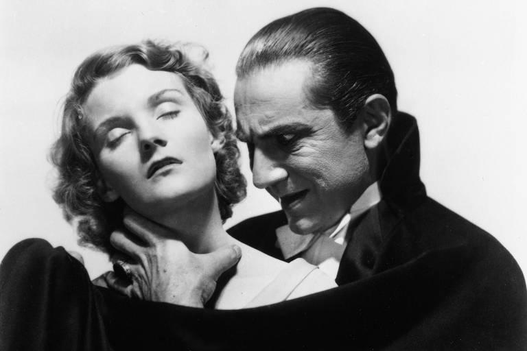 Vestido de vampiro, ator segura no pescoço de mulher inconsciente, e a olha como se estivesse prestes a morder
