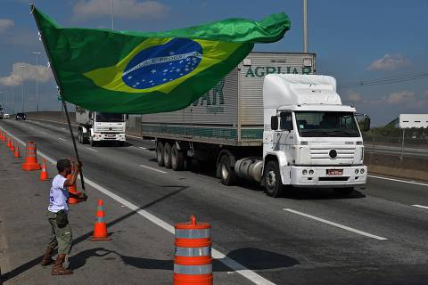 TOPSHOT - A protestor waves the Brazilian national flag outside the Duque de Caxias refinery in metroplitan Rio de Janeiro, Brazil, on May 28, 2018, where soldiers have been deployed to guarantee the safe transport of fuel for essential services.