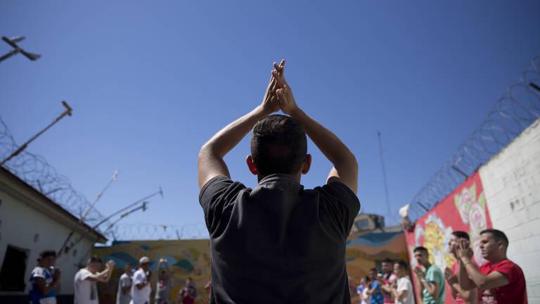 Detentos em pátio colorido levantam as mãos juntas (lembrando a posição de oração), para desenvolver uma posição de ioga