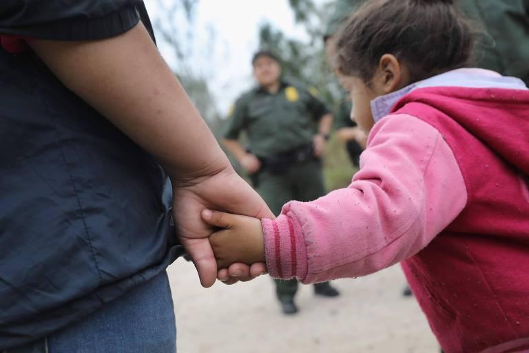 Mulher de casaco azul marinho e calça jeans segura pelas mãos uma menina de casaco rosa escuro com mangas rosa claro. Aparecem na imagem as mãos das duas e, ao fundo, um guarda de fronteira de roupa verde.