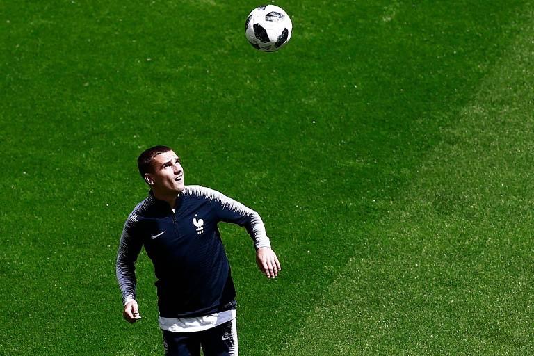 Antoine Griezmann no campo de futebol olhando para bola no ar, pronto para cabeceá-la